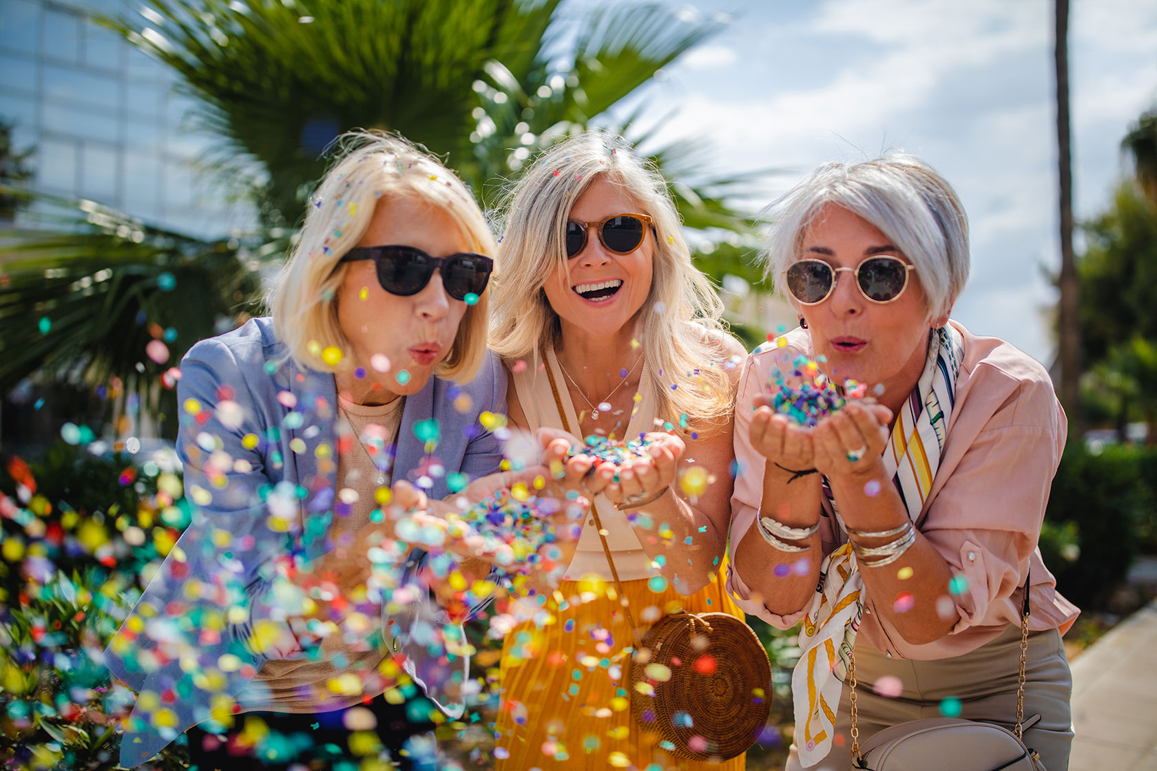 Three older women in sunglasses blowing confetti